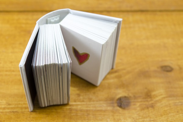 Small open book with a heart shape on a page shot against a wooden surface